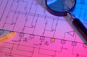 electrical blueprints with magnifying glass and highlighter sitting on them