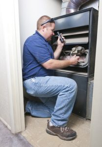 male technician working on the inside of a furnace
