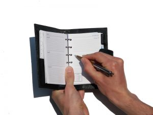 hands filling out planner on an isolated white background