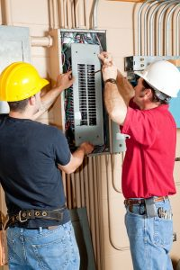 two electricians inspecting electrical panel