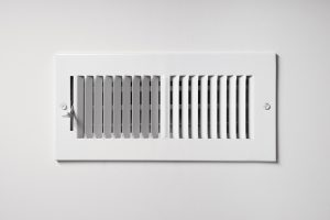 A heating/cooling vent register on the wall of a home, with open/close lever