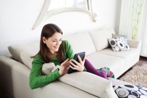 Image of young woman relaxing and using digital tablet