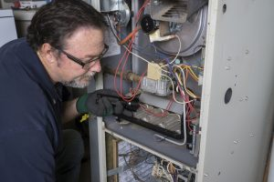 technician-looking-over-gas-powered-furnace