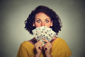 Scared looking woman hiding picking through dollar banknotes