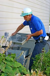 tech-servicing-outdoor-ac-unit